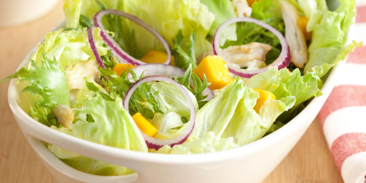 em uma mesa de madeira contém um recipiente branco que comporta a salada. Ao lado um pote com tempero e um pano listrado nas cores branco e rosa.