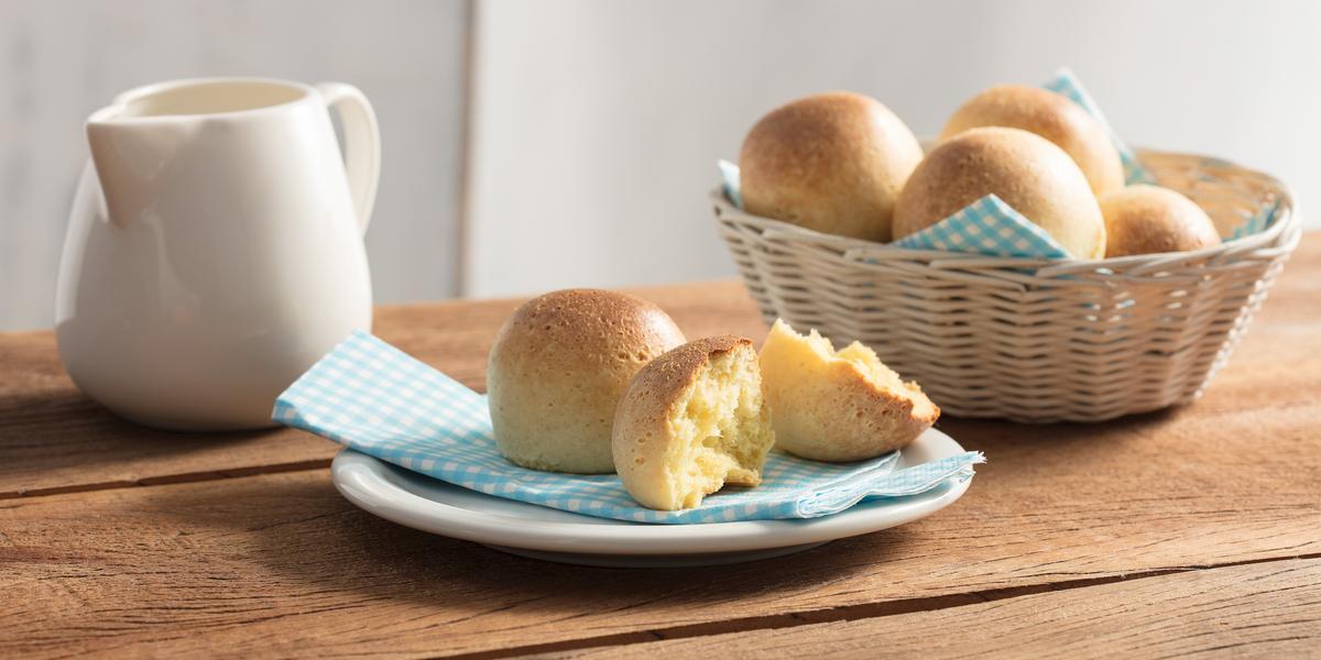 Fotografia em tons de azul em uma bancada de madeira com um prato branco raso e um guardanapo de papel azul com bolinhas brancas e o pãozinho de ninho em cima e cortado ao meio. Ao lado, uma cesta de vime com mais pãezinhos de ninho.