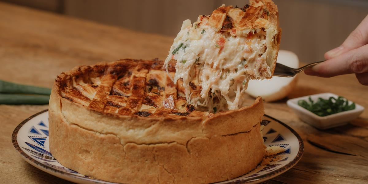 Fotografia em tons de marrom de uma bancada de madeira com um prato raso branco com detalhes azul sobre ele um quiche de frango com um pedaço sendo cortado. Ao fundo um potinho branco quadrado com cebolinha e uma cebola.
