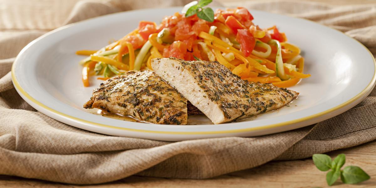 Fotografia em tons de marrom em uma mesa de madeira com um pano marrom, um prato branco raso redondo com detalhes em dourado e o macarrão de legumes acompanhado de filé de frango em cima dele.