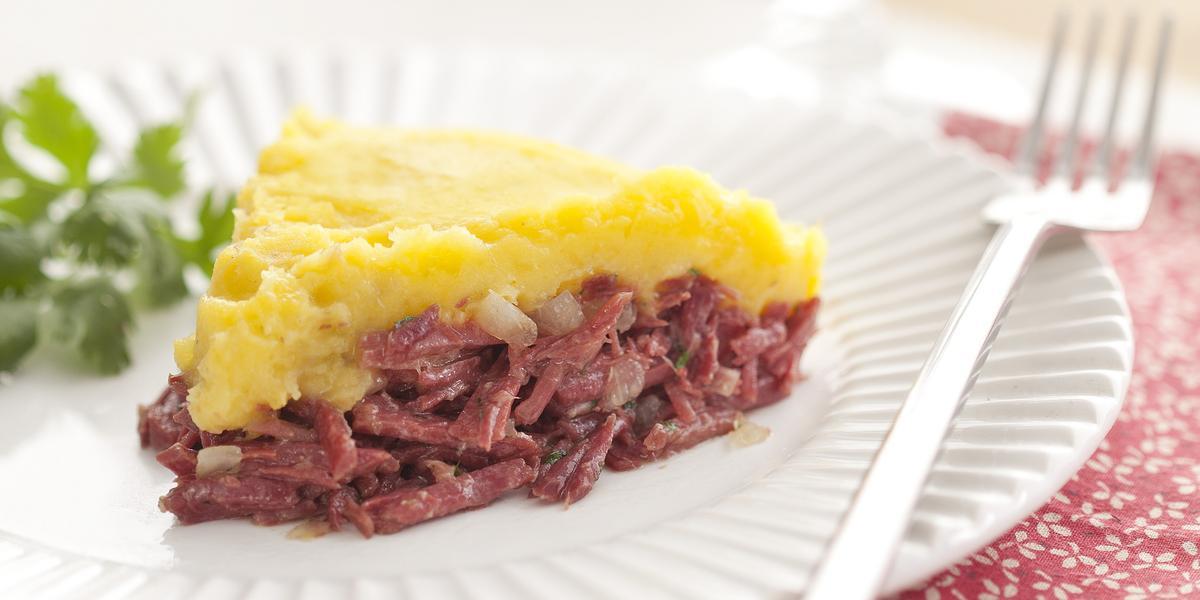 Fotografia em tons de vermelho em uma mesa de madeira clara com um prato redondo raso branco ao centro com uma fatia do escondidinho de carne seca com mandioquinha e coentro ao lado para enfeitar o prato.