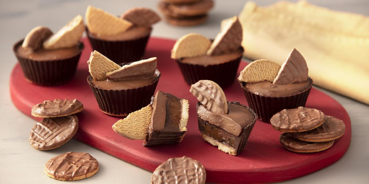 Foto de uma bancada branca. Sobre ela há uma tábua vermelha com seis unidades da receita pronta, além de alguns Biscoitos Calipso Cobertos com Chocolate.