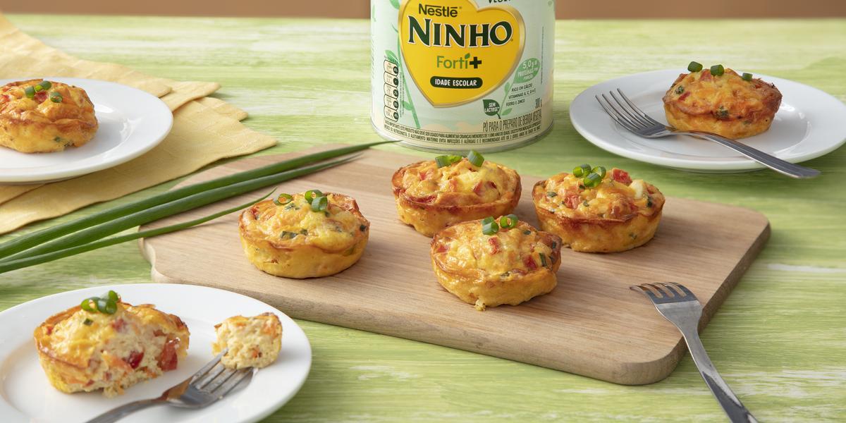 Fotografia em tons de verde e amarelo de uma bancada de madeira, ao centro uma tábua de madeira com 4 omeletes redondos, ao fundo uma lata de NINHO Origem Vegetal e ao redor mais omeletes.
