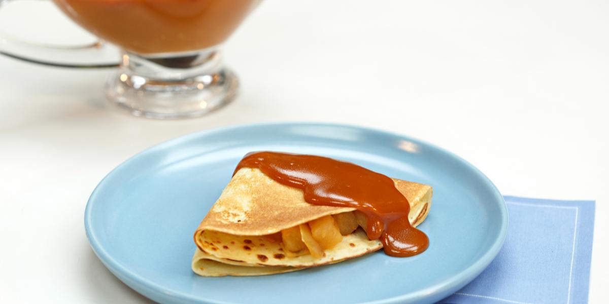 em um prato redondo e azul contém um creme com cobertura de caramelo por cima e abaixo do prato dois panos azuis. Ao fundo, um recipiente transparente com caramelo.