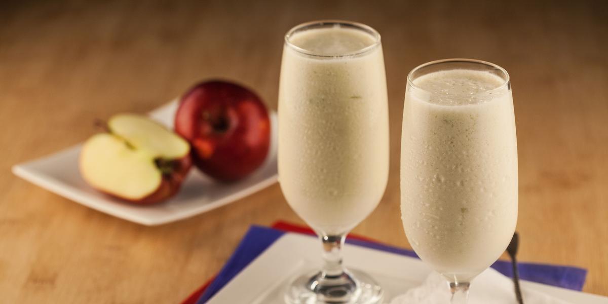 Fotografia em tons de azul e vermelho em uma bancada de madeira com um pano azul e um vermelho embaixo de um prato quadrado branco e duas taças de vidro com a bebida de maçã em cima. Ao fundo, uma maçã cortada ao meio e outra inteira.