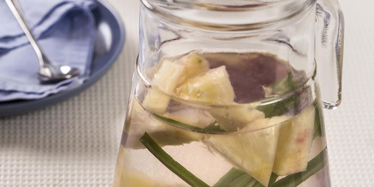 Fotografia em tons de cinza e azul de uma bancada branca vista de cima, uma jarra transparente com agua Capim-santo e Abacaxi. Ao fundo dois pratos azuis com panos azuis por cima e um copo transparente.