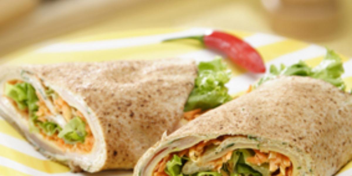 Em um prato na cor amarelo e branco contém dois sanduíches.