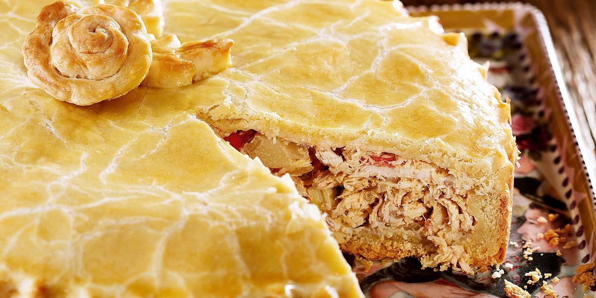 Foto de uma torta de frango com uma fatia a menos em cima de um prato decorado