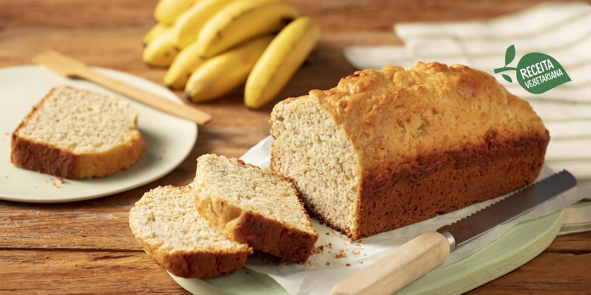 Fotografia em tons de marrom, verde e branco de uma bancada de madeira com uma tabua verde, sobre ela uma faca e o pão de banana. Ao fundo um prato branco com uma fatia de bolo e uma espátula, um cacho de banana e um paninho branco com listras verdes.