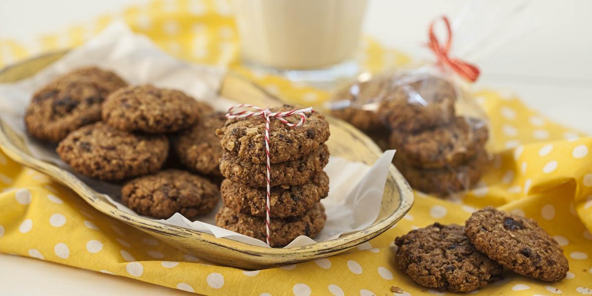Fotografia em tons de branco e amarelo de uma bancada branca com um paninho amarelo com bolinhas brancas, sobre ele cookies. Ao fundo um copo de vidro.