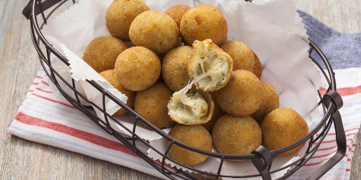 Fotografia em tons cinza, branco e dourado, mostrando bancada em tons de cinza com cestinha de arame contendo bolinhas de queijo fritas sobre papel toalha e guardanapo branco com listras vermelhas.