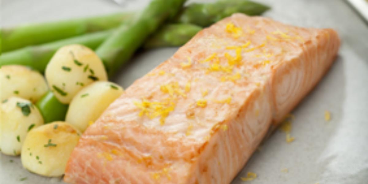 Fotografia em tons de amarelo em uma bancada de madeira com um prato bege ao centro, uma posta de salmão, aspargos e batatas bolinhas