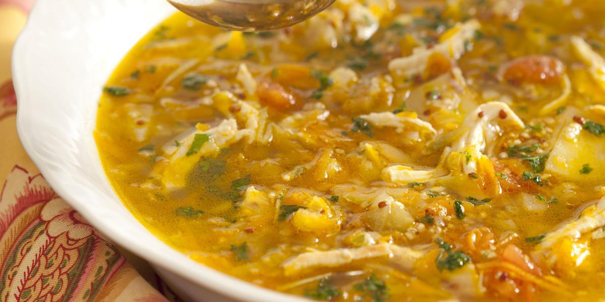 Em uma mesa de madeira cinza, contém um prato branco que comporta a canja de galinha e ao lado um pano florido nas cores amarelo e rosa.