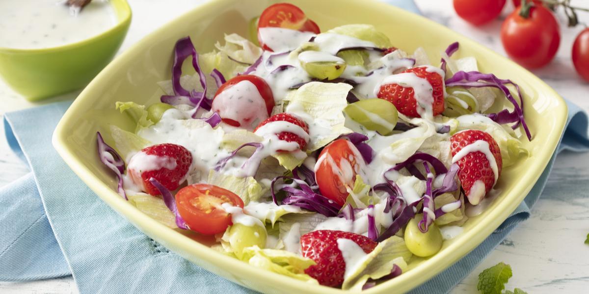 Fotografia em tons de branco, azul e verde de uma bancada branca e um paninho azul, sobre ele um recipiente quadrado verde com a salada e o molho. Ao fundo um recipiente quadrado verde com o molho, uma colher e tomatinhos cereja.