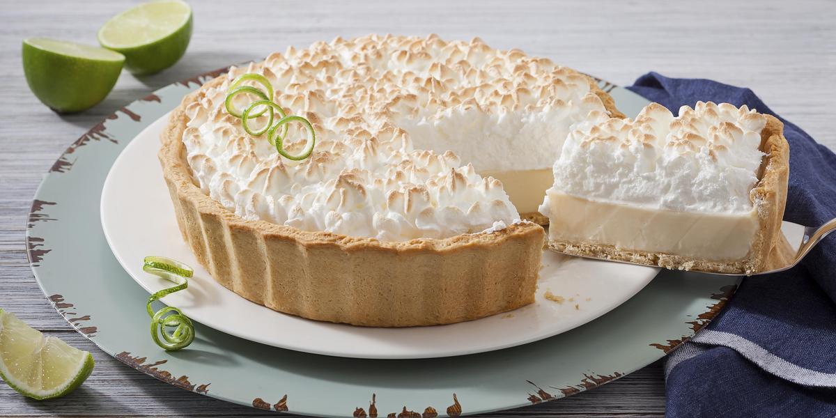 Foto de uma torta de limão em cima de um prato branco e com uma fatia generosa sendo retirada