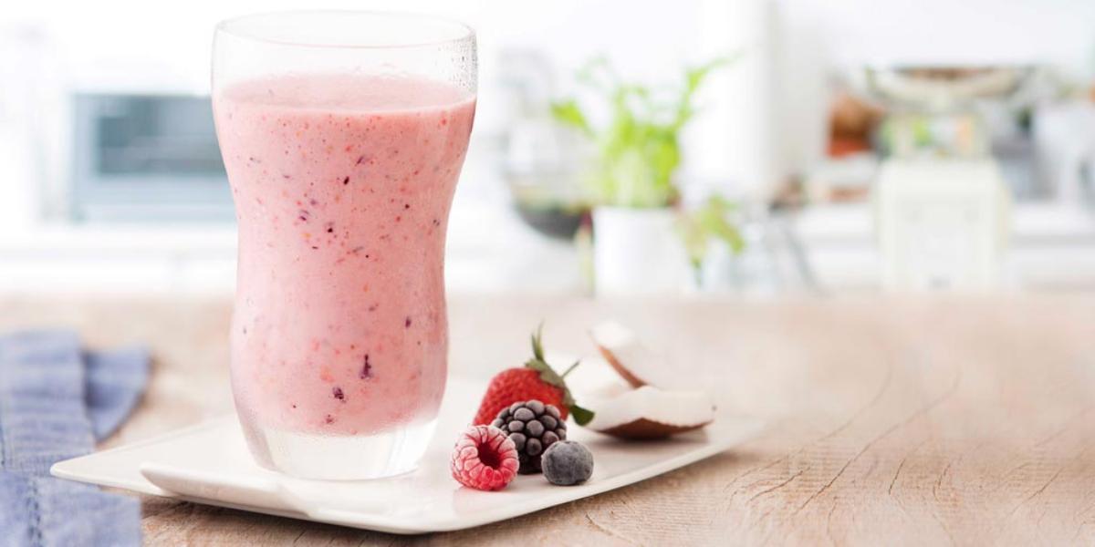fotografia e tons de rosa e branco de uma bancada bege vista de frente, contém um copo transparente com a bebida de frutas vermelhas e ao lado contém frutas vermelhas.