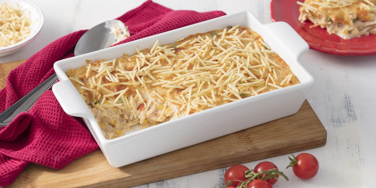 Fricassê em uma forma branca em cima de uma tábua de madeira, com tomates cereja decorando e um pano rosa do lado