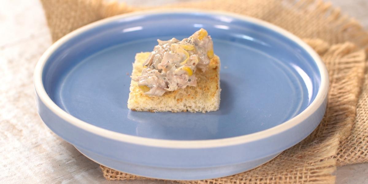 Fotografia em tons de branco, marrom e azul de uma bancada branca, com um paninho marrom, sobre ele um prato de vidro azul com o mini sanduíche.
