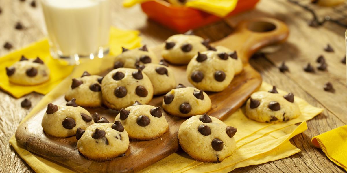 Fotografia em tons de marrom e amarelo de uma bancada de madeira com um paninho amarelo, sobre ela uma tábua de madeira com cookies. Ao fundo um copo de vidro com leite e um recipiente vermelho com um paninho amarelo com cookies.