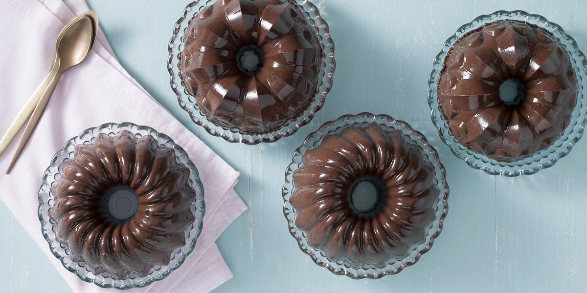 Fotografia em tons de chocolate, azul e rosa, com quatro porções de pudim de chocolate em pratinhos de cristal, um deles sobre guardanapo rosa tendo ao lado colheres de sobremesa, tudo sobre bancada azul.