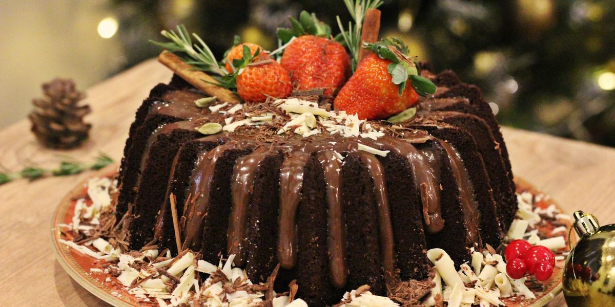 Fotografia em tons de marrom e vermelho de uma bancada de madeira clara, sobre ela um prato vermelho redondo com o bolo de chocolate decorado. Ao lado uma bolinha natalina e uma pinha.