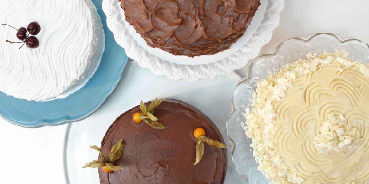 4 bolos com diferentes sabores por cima de pratos onde 2 são de vidros um é branco e o outro azul.