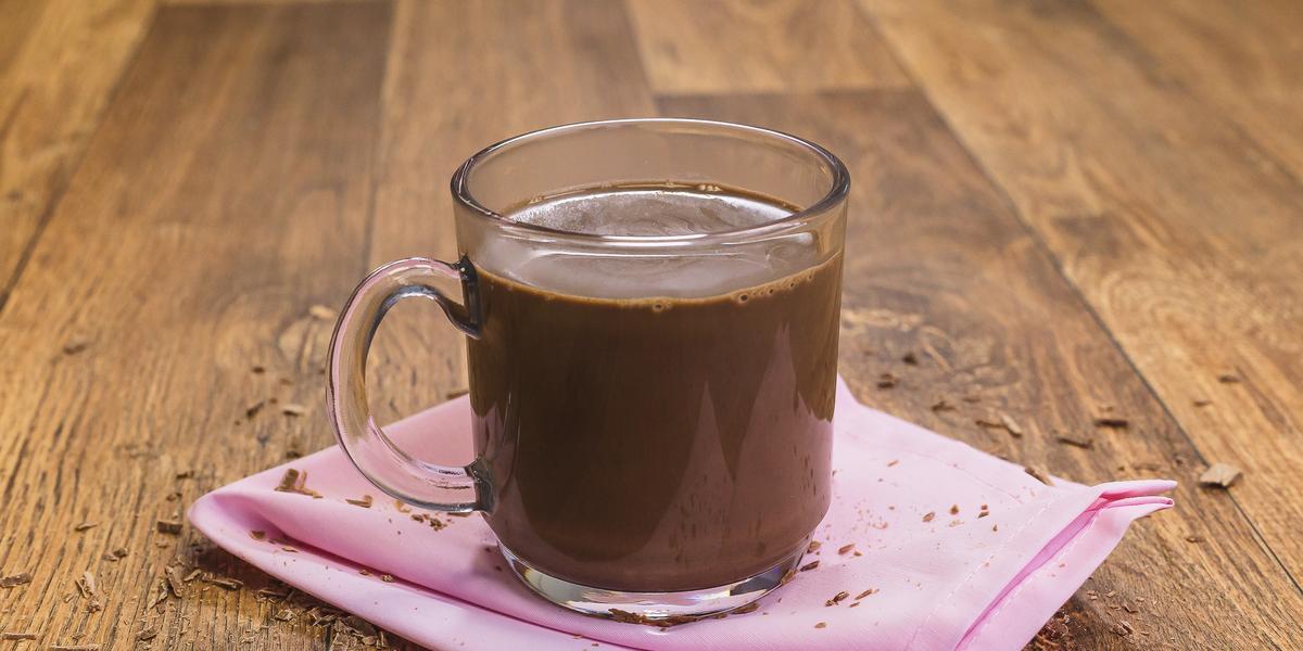 Fotografia de uma bancada de madeira com um paninho rosa e uma xícara transparente com o chocolate quente dentro.