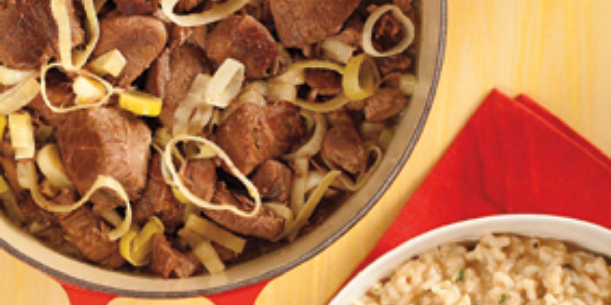 Fotografia em tons de vermelho em uma bancada de madeira amarela, um pano vermelho, um prato branco com risoto. Ao lado, uma panela vermelha funda com o carneiro ao molho de vinho tinto e alho-poró.