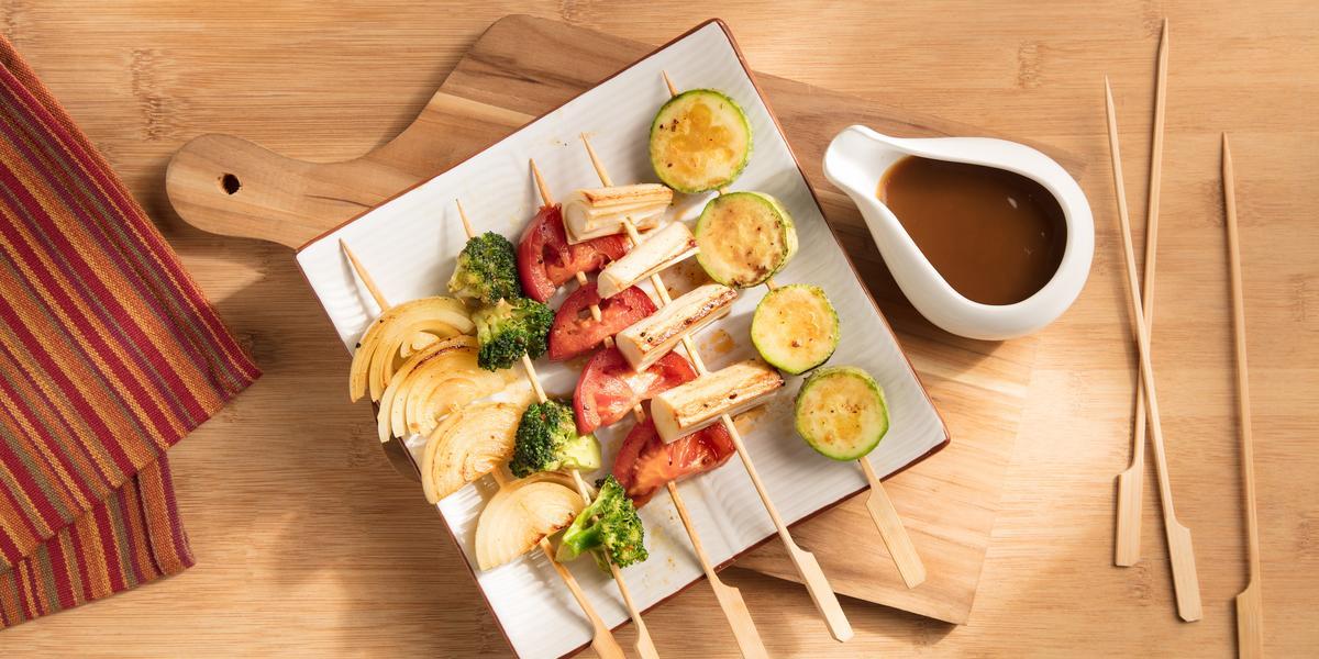 Fotografia em tons de laranja em uma mesa de madeira, uma tábua de madeira, um pano listrado com cores alaranjada e um prato quadrado com vários espetinhos de legumes. Ao lado, um potinho com o molho shoyu.