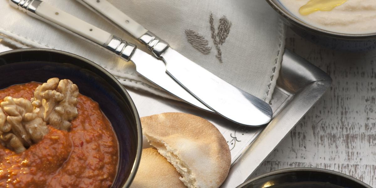 Fotografia em tons de bege em uma bancada de madeira clara com uma bandeja ao centro, três facas apoiadas nela. Três recipientes com comidas árabes, babaganush, mhamara e hommus.