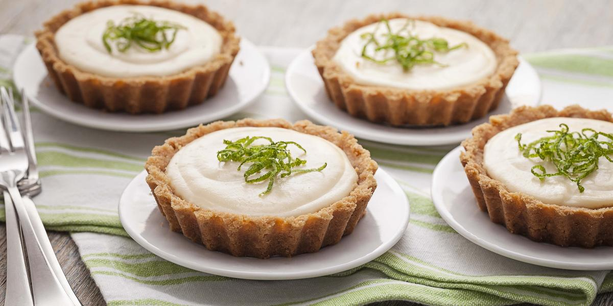 Fotografia em tons de verde em uma mesa de madeira com um pano listrado em verde e quatro pratinhos brancos cada um com a torta creme de limão. Ao lado, três garfos.