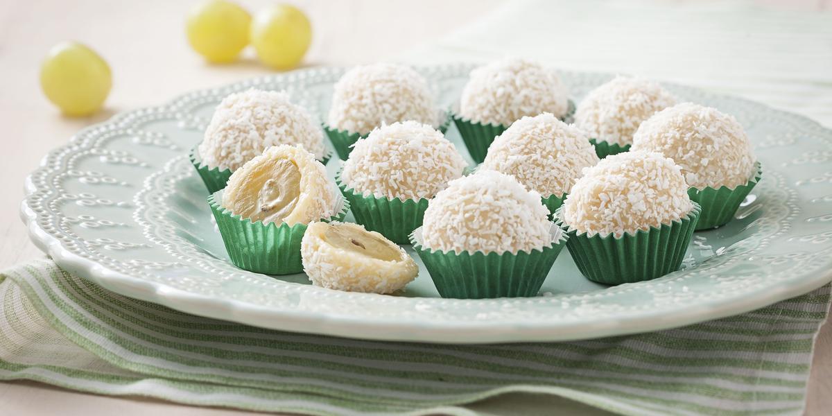 Fotografia em tons de verde e branco de uma bancada vista de frente, contém um pano listrado em verde e branco, um prato redondo branco com vários beijinhos em forma de bolinha com coco por cima.