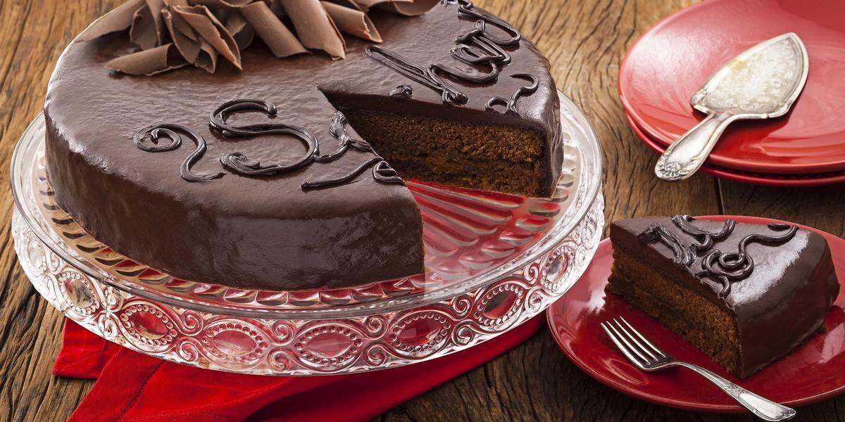 Fotografia em tons de vermelho em uma bancada de madeira com um suporte para bolo de vidro com a torta sacher de chocolate em cima cortada ao meio. Ao lado, pratinhos vermelhos e um deles com uma fatia da torta.