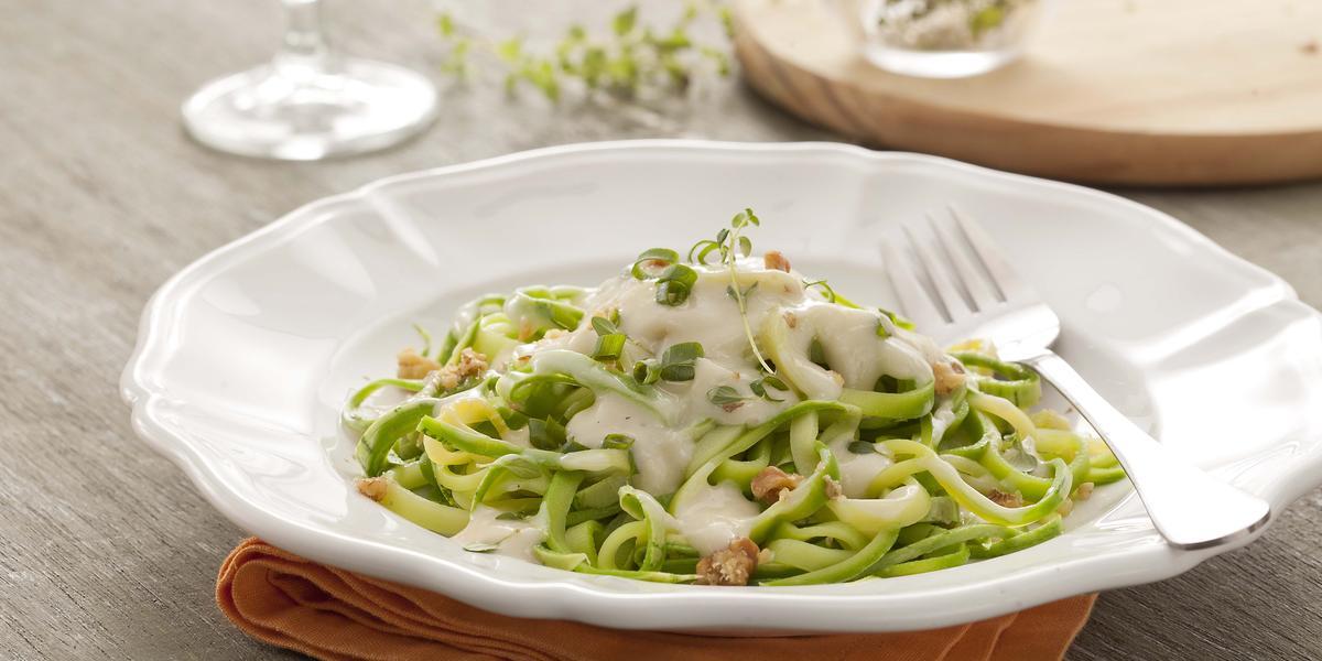Fotografia em tons de verde e branco, ao centro um prato branco fundo com o espaguete de abobrinha verde dentro com molho branco. Abaixo do prato está um guardanapo de tecido laranja em uma mesa de madeira.