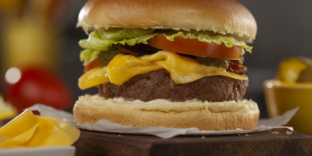 Fotografia em tons de marrom de uma bancada de madeira, sobre ela uma tábua de madeira com um papel e um hambúrguer. A frente um recipiente branco com uma fatia de queijo.
