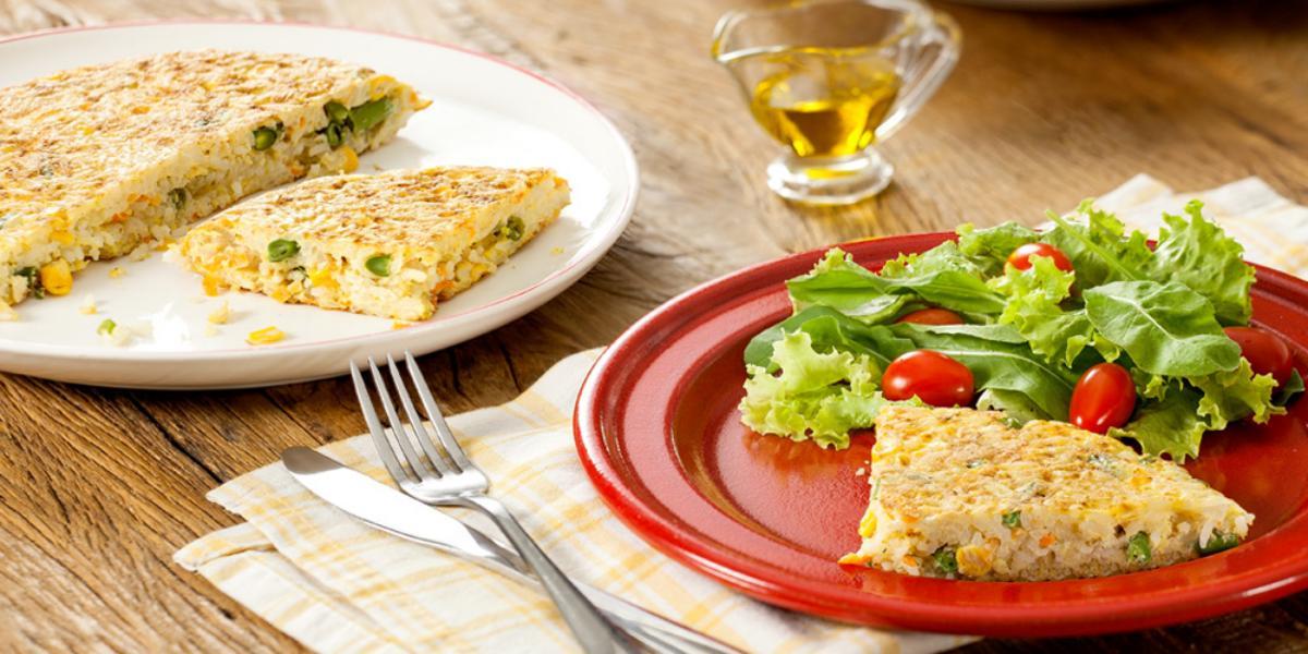 Fotografia em tons de vermelho e amarelo em uma bancada de madeira com um prato branco raso redondo ao fundo com a tortilla de arroz e ao lado, um prato vermelho com uma fatia da tortilla e salada de alface e tomate cereja.