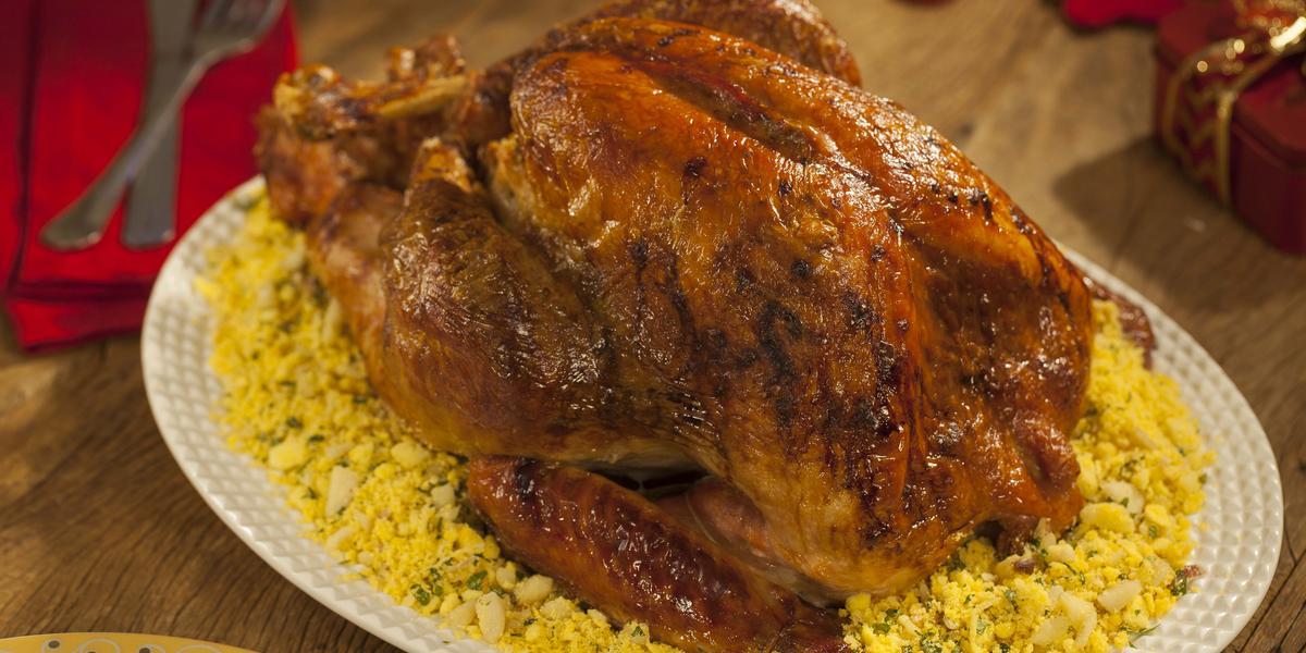 Fotografia em tons de marrom e branco de uma bancada de madeira, sobre ela um prato oval branco com um peru e farofa. Ao fundo um paninho vermelho, um garfo e uma faca.