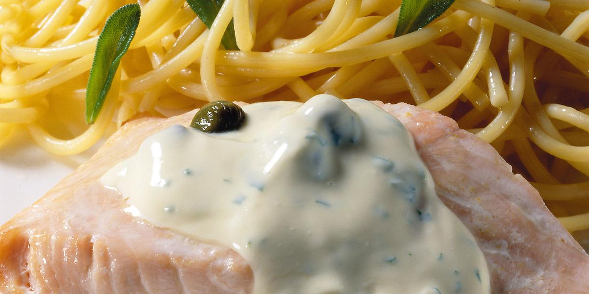 Uma mesa azul com bolinhas brancas vista de cima, um prato quadrado branco com macarrão espaguete, um pedaço de salmão com molho branco por cima.