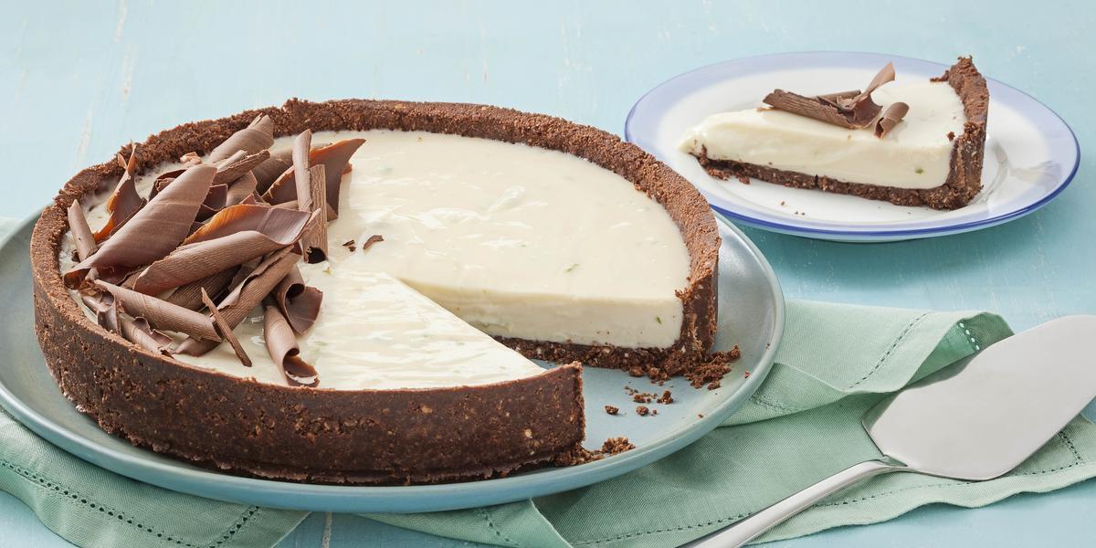 Fotografia em tons de azul em uma mesa de madeira azul com um prato raso azul claro e a torta de limão e chocolate. Ao lado, um prato pequeno com uma fatia da torta e uma espátula de bolo.