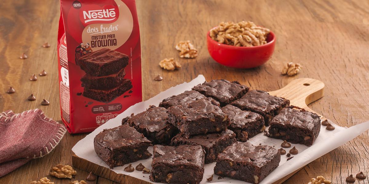 Fotografia em tons de marrom e vermelho de uma bancada de madeira com uma tábua e um papel manteiga, sobre ele pedaços de brownie. Ao fundo um recipiente vermelho pequeno com nozes e um pacote de brownie dois frades.