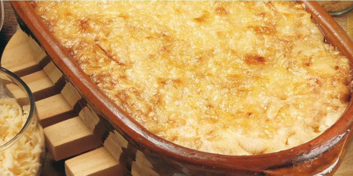 Fotografia em tons de marrom em uma bancada com um suporte para panela de madeira, uma travessa de barro com as cebolas gratinadas dentro dela e em cima do suporte. Ao lado, potinho com queijo ralado.