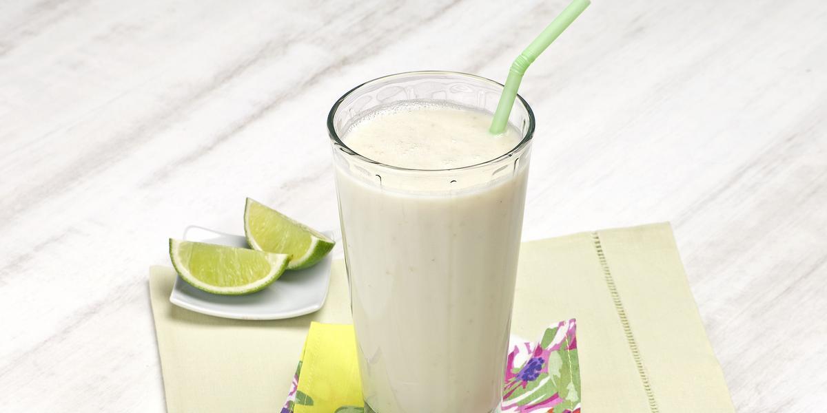 Fotografia em tons de verde em uma bancada de madeira cinza clara com um pano bege com detalhes verdes, um pratinho branco pequeno com um copo de vidro longo e grande com o smoothie de pera com limão. Ao lado, duas fatias de limão.