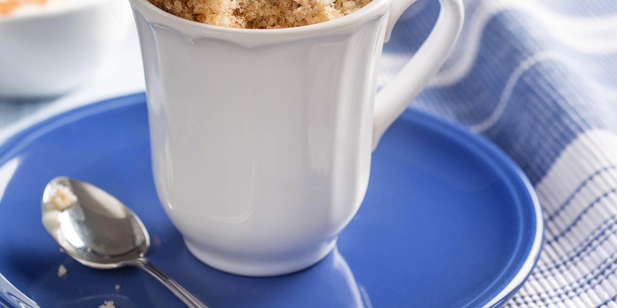 Fotografia em tons de branco e azul, com caneca branca ao centro contendo bolo e uma colher sobre prato azul, ao lado guardanapo em branco e azul, acima potinho com iogurte, tudo sobre bancada em tons de azul.