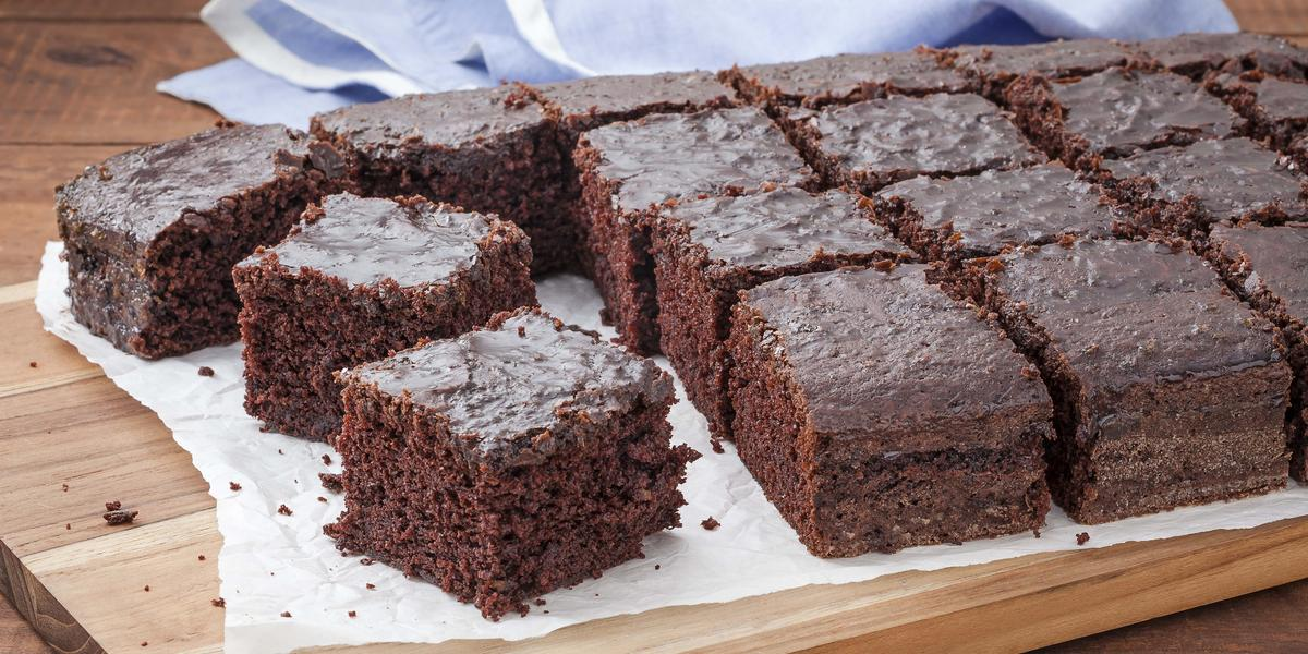 16 pedaços de bolo de chocolate com calda em cima de uma toalha branca que está em cima de uma tábua de madeira. Todos do mesmo tamanho