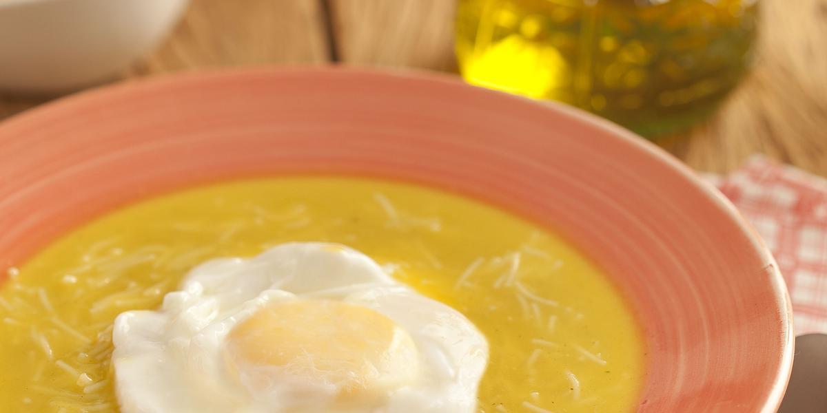 Fotografia em tons de laranja em uma bancada de madeira escura, um pano desenhado laranja, um prato laranja com a sopa portuguesa com ovo pochê dentro dele. Ao fundo, um vidrinho de azeite e um potinho com queijo ralado.