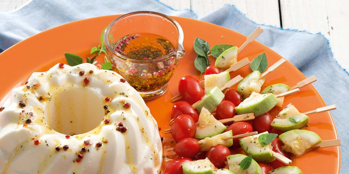 Fotografia em tons de branco, laranja e azul com prato laranja contendo mini espetinhos de vegetais, potinho com molho e uma terrine branca, sobre guardanapo azul e bancada na cor branca.