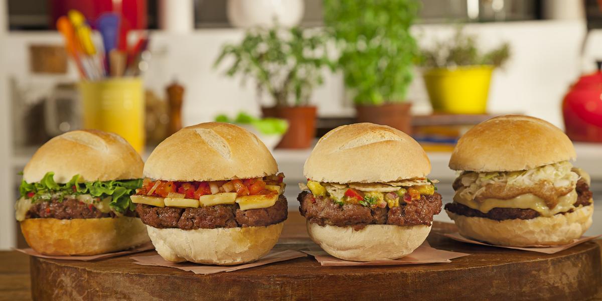 Fotografia em tons de marrom de uma bancada marrom com uma tábua de madeira, sobre ele quatro hamburgueres.