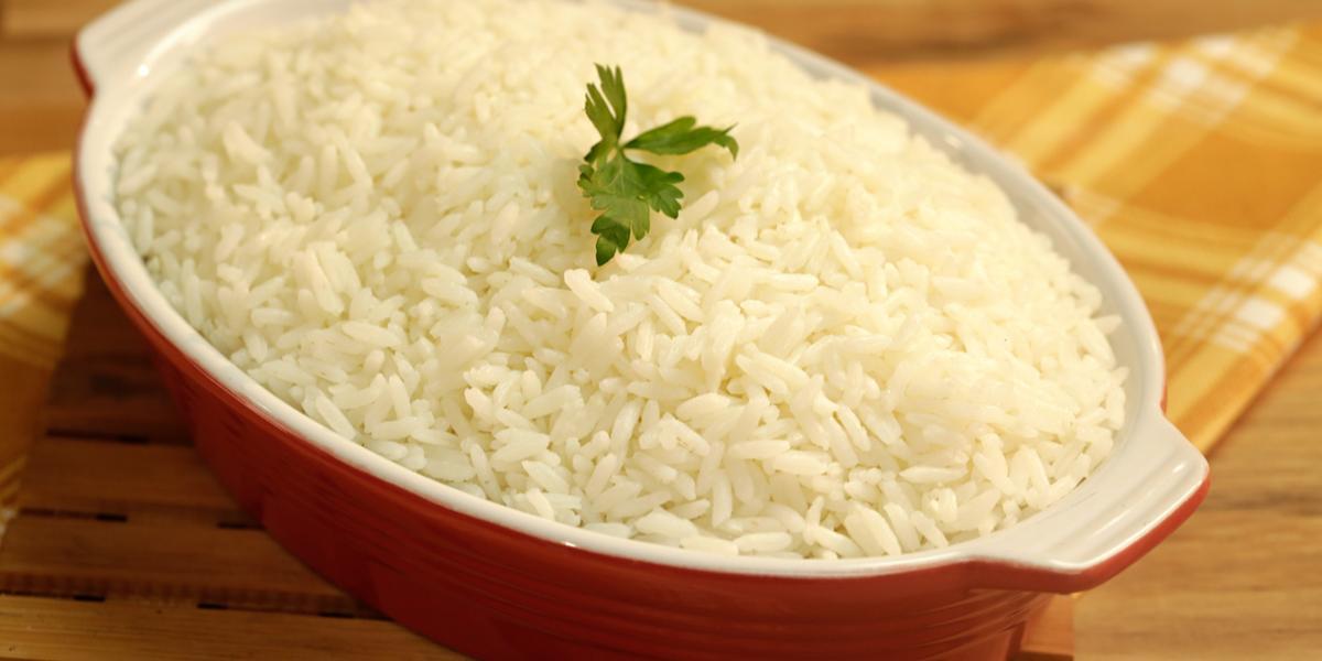 Foto de um recipiente vermelho com arroz branco dentro e uma folha de coentro decorando