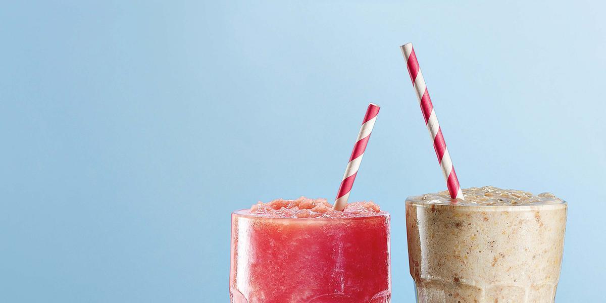 Fotografia em tons de azul e roxo vista de frente. Dois copos transparentes um com uma bebida de cor rosa e o outro com vitamina na cor cinza e ambos contém um canudo vermelho e branco.