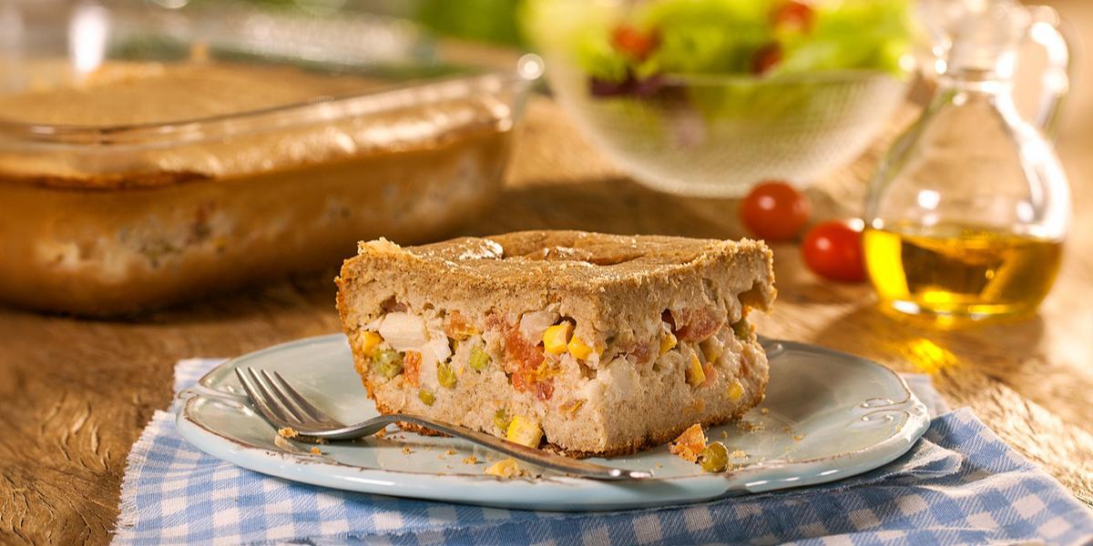 Fotografia em tons de marrom em uma bancada de madeira com um pano xadrez azul e um prato branco com um pedaço de torta integral de legumes. Ao fundo, uma travessa com a torta inteira, um potinho com salada e um vidro de azeite.